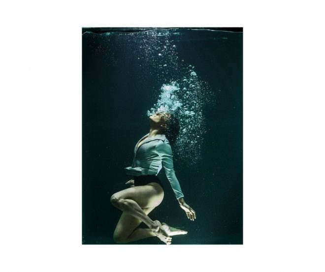 The affect of stress on breathing patterns. A young woman exhales a stream of bubbles underwater