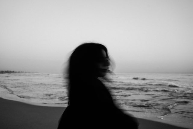 blurred black and white image of a woman at the beach. Photo by Enric Cruz López